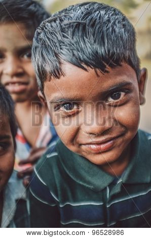 HAMPI, INDIA - 31 JANUARY 2015: Indian boy with friends in background. Post-processed with grain, texture and colour effect.