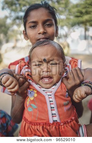 HAMPI, INDIA - 31 JANUARY 2015: Indian baby with bindi cries while being held by family member. Post-processed with grain, texture and colour effect.