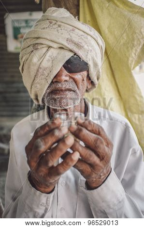 HAMPI, INDIA - 31 JANUARY 2015: Blind elderly Indian man with sunglasses and headscarf holds a glass of chai. Post-processed with grain, texture and colour effect.