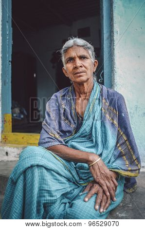HAMPI, INDIA - 31 JANUARY 2015: Elderly Indian woman sits in sari in-front of home. Post-processed with grain, texture and colour effect.