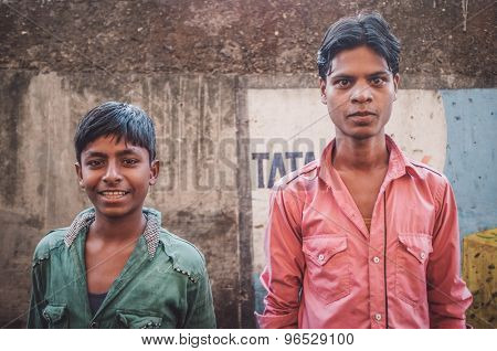 MUMBAI, INDIA - 12 JANUARY 2015: Young Indian men in Dharavi slum. Post-processed with grain, texture and colour effect.