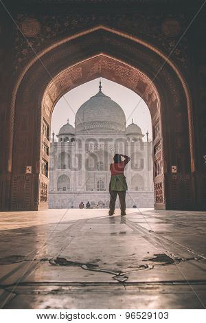 AGRA, INDIA - 28 FEBRUARY 2015: View of Taj Mahal from mosque. Woman photographing Taj. West side. Post-processed with grain, texture and colour effect.