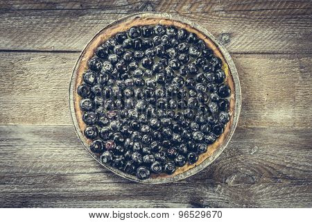 Tart with blueberries on a wooden background. top view