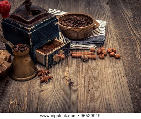 old grinder and coffee beans on a wooden background
