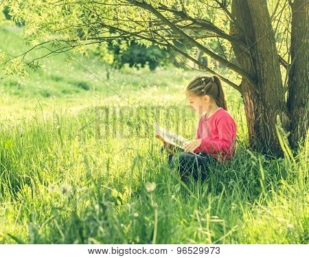 Cute little girl read the book under tree