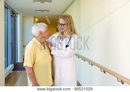 Nurse Assisting Elderly Woman Walking At Corridor