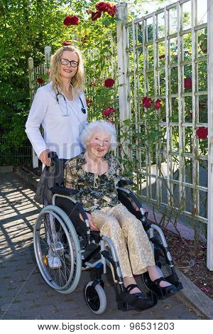 Nurse And Elderly On Wheelchair Smiling At Camera