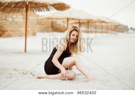 Portrait Of A Sexy Blond Woman Dreaming On A Summer Evening On A Sandy Tropical Beach