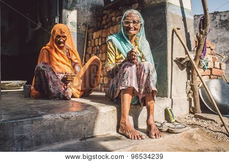 GODWAR REGION, INDIA - 13 FEBRUARY 2015: Two elderly Indian woman in sari's with covered heads sit in doorway of home. Post-processed with grain, texture and colour effect.