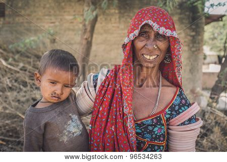 GODWAR REGION, INDIA - 15 FEBRUARY 2015: Elderly Indian tribeswoman wears traditional clothes decoration. Baby has flies around mouth and nose. Post-processed with grain, texture and colour effect.
