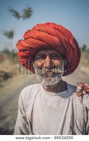 GODWAR REGION, INDIA - 14 FEBRUARY 2015: Elderly Rabari tribesman with big red turban stands on road. Post-processed with grain, texture and colour effect.