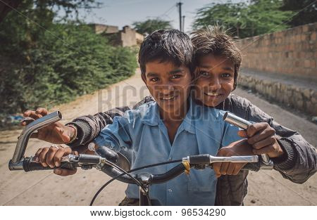 GODWAR REGION, INDIA - 15 FEBRUARY 2015: Two boys on a bicycle in empty village street. Post-processed with grain, texture and colour effect.