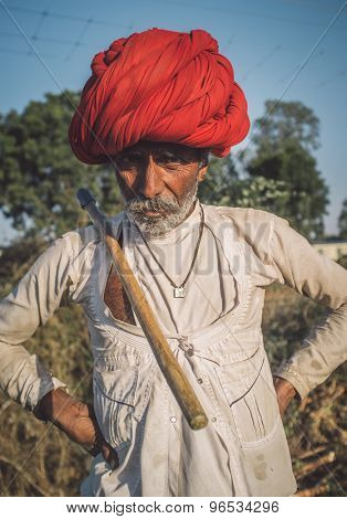 GODWAR REGION, INDIA - 14 FEBRUARY 2015: Elderly Rabari tribesman with red turban and traditional ax on shoulders. Post-processed with grain, texture and colour effect.