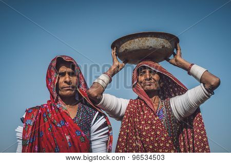 GODWAR REGION, INDIA - 14 FEBRUARY 2015: Rabari tribeswomen stand in field wearing sarees and upper-arm bracelets. One balances bucket on head. Post-processed with grain, texture and colour effect.