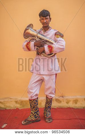 GODWAR REGION, INDIA - 15 FEBRUARY 2015: Young Indian musician dressed in wedding ceremony outfit holds trumpet. Post-processed with grain, texture and colour effect.