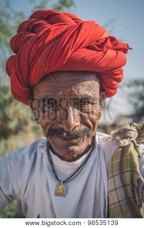 GODWAR REGION, INDIA - 14 FEBRUARY 2015: Elderly Rabari tribesman with red turban. Post-processed with grain, texture and colour effect.