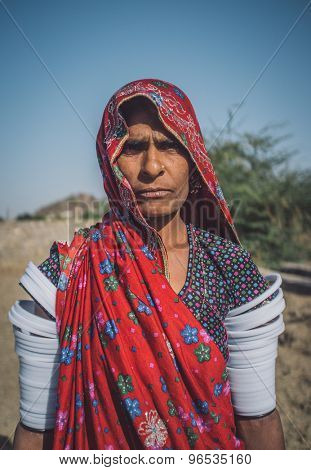 GODWAR REGION, INDIA - 14 FEBRUARY 2015: Rabari tribeswoman stands in field wearing saree and upper-arm bracelets. Post-processed with grain, texture and colour effect.