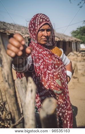 GODWAR REGION, INDIA - 13 FEBRUARY 2015: Rabari tribeswoman in sari decorated with traditional upper-arm bracelets holds gate of stable. Post-processed with grain, texture and colour effect.