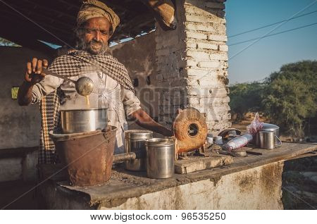 GODWAR REGION, INDIA - 14 FEBRUARY 2015: Man prepares milk tea with traditional wind turbine for making fire. Post-processed with grain, texture and colour effect.