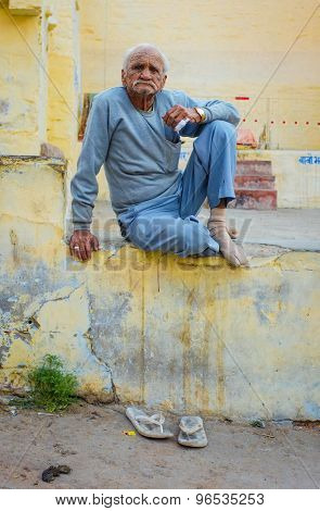 JODHPUR, INDIA - 07 FEBRUARY 2015: Elderly man sitting cross-legged on wall with slippers below him in dirty street. Common scene to see people hanging out on Jodhpur streets in late afternoon.
