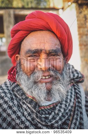 GODWAR REGION, INDIA - 14 FEBRUARY 2015: Elderly Rabari tribesman with red turban and blanket around the shoulders. Post-processed with grain, texture and colour effect.