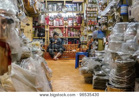 JODHPUR, INDIA - 07 FEBRUARY 2015: Shop owner with hat sitting on couch and resting before closing time. Stores with kitchen pottery and other products made from metal are common on Asian markets.