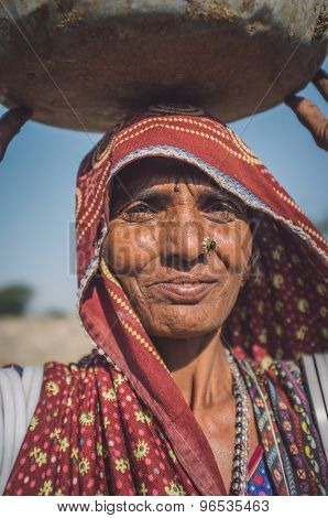 GODWAR REGION, INDIA - 14 FEBRUARY 2015: Rabari tribeswoman stands in field wearing saree and upper-arm bracelets. Balances bucket on head. Post-processed with grain, texture and colour effect.
