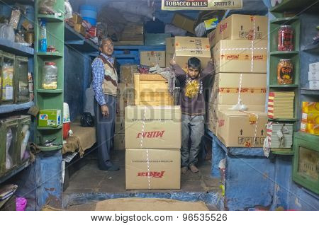 JODHPUR, INDIA - 07 FEBRUARY 2015: Shop owner and young worker in storeroom of tobacco shop with Miraj chewing tobacco in boxes. Miraj produces the finest quality chewing tobacco.