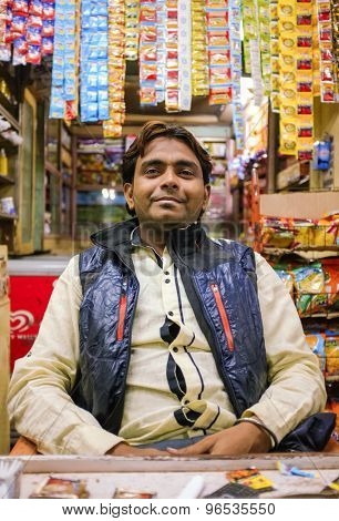 MUMBAI, INDIA - 05 FEBRUARY 2015: Portrait of Indian vendor sitting in shop with gutka hanging in background.