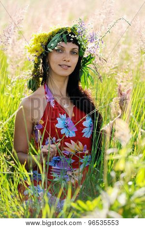 Smiling Brunette Woman With Long Black Hair Sitting In Grass With Wreath On Her Head In Summer Meado
