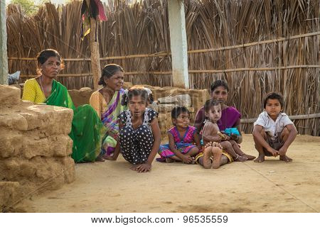 HAMPI, INDIA - 31 JANUARY 2015: Rural indian family sitting on ground in evening shade in home courtyard.