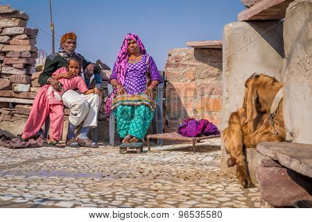 JODHPUR, INDIA - 09 FEBRUARY 2015: Grandparents rest with granddaughter on roof terrace of home with goat sitting close by.