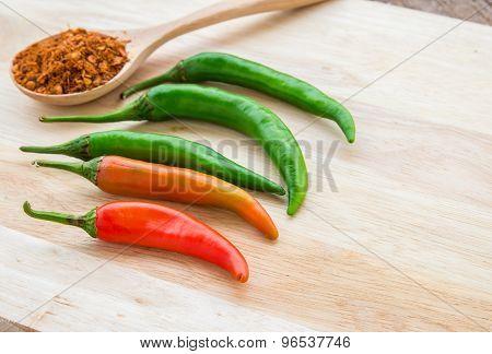 Chili Powder And Fresh Chili On Cutting Board
