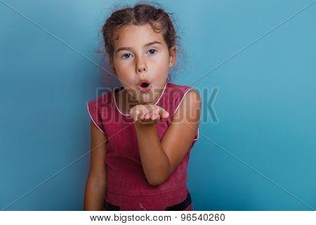 Girl European appearance decade kiss on a blue  background