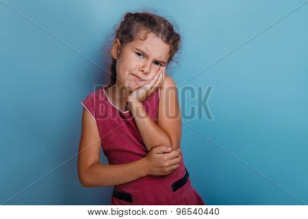Girl European appearance decade toothache on a blue  background