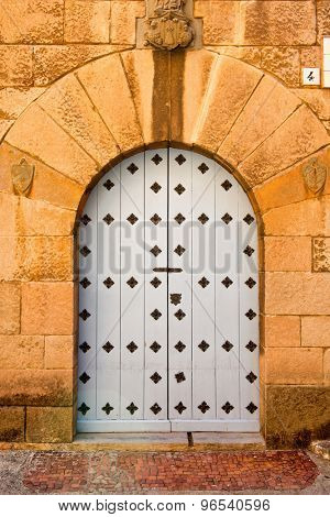 Ornate arched stone door decorated in a diamond pattern
