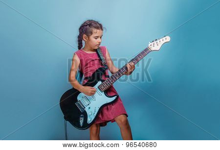 Girl European appearance ten years playing guitar on a blue back