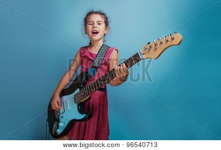 Girl European appearance ten years playing guitar sings on a blu