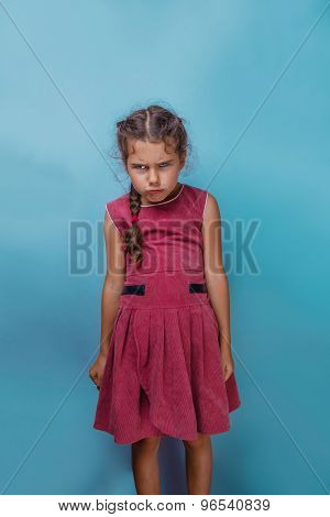 Girl European appearance decade angry frowns on blue background