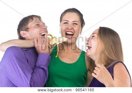 Photo of three happy friends with banana