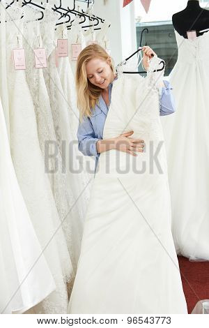Bride Choosing Dress In Bridal Boutique