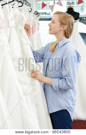 Bride Looking At Price Tag On Wedding Dress In Bridal Boutique