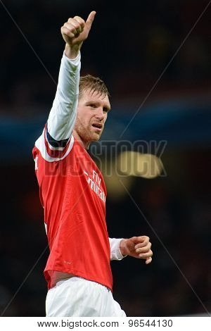 LONDON, ENGLAND - Nov 26 2013: Arsenal's Per Mertesacker salutes the fans at the end of the match at the UEFA Champions League match between Arsenal and Olympique  played at The Emirates Stadium