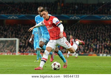 LONDON, ENGLAND - Nov 26 2013: Arsenal's Mesut Ozil crosses the ball during the UEFA Champions League match between Arsenal and Olympique de Marseille, at The Emirates Stadium