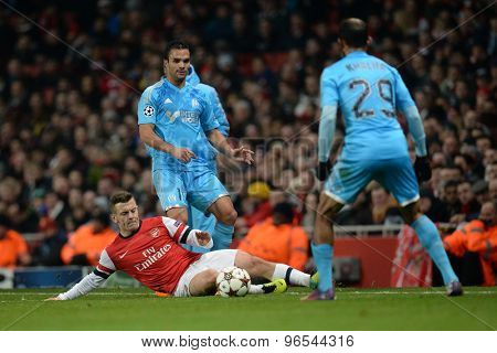 LONDON, ENGLAND - Nov 26 2013: Arsenal's Jack Wilshere slides on the floor to intercept a pass during the UEFA Champions League match between Arsenal and Olympique de Marseille
