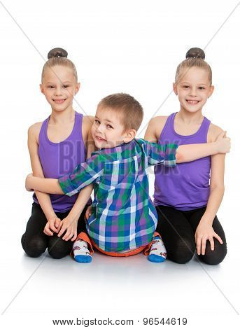 Brother hugs his sisters