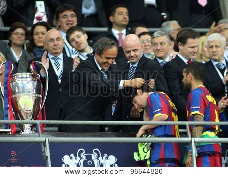 LONDON, ENGLAND. May 28 2011: Barcelona's forward Lionel Messi gets his winners medal from UEFA President Michel Platini after winning the 2011UEFA Champions League final