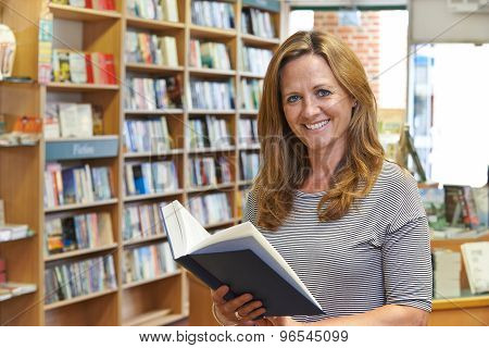Portrait Of Female Customer Reading Book In Bookstore