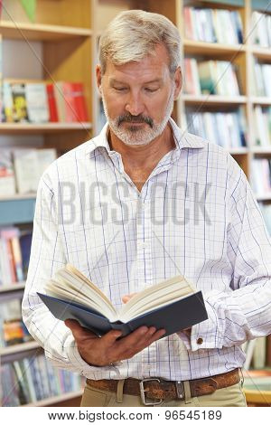 Male Customer Reading Book In Bookstore