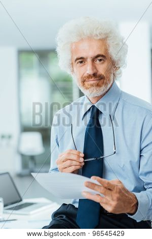 Confident Businessman Reading Paperwork